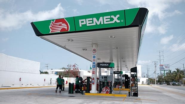 Trabajadores de Pemex llevan mascarilla mientras sirven a un taxi en Cancún